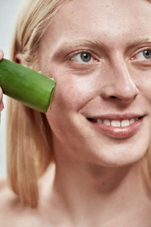 Portrait of smiling young caucasian man with aloe leaf 免版税图像