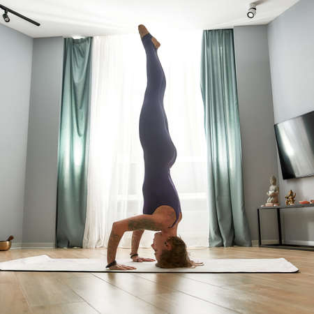 Side view of flexible young woman in tight bodysuit practicing yoga, doing Handstand pose, exercising on a mat in modern apartment 免版税图像