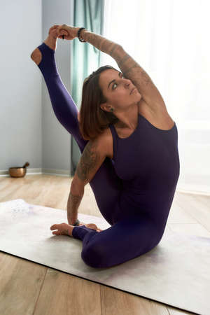 Sportive young woman in tight bodysuit looking away, practicing yoga, doing Compass pose while exercising on a mat in living room at home on a daytime