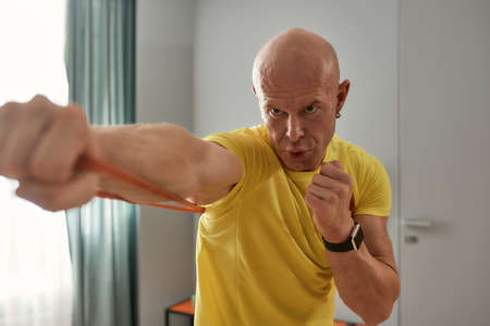Bald coach doing boxing at home in self-isolation 免版税图像