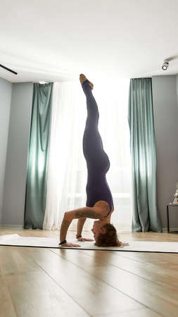 Full length shot of flexible young woman in tight bodysuit practicing yoga, doing Handstand pose, exercising on a mat in modern apartment