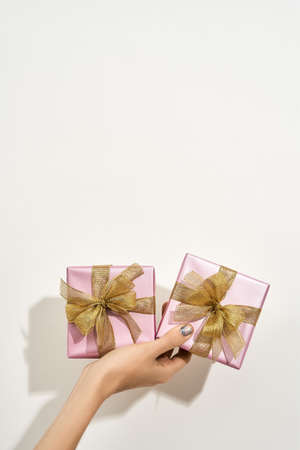 Happy Womens day. Vertical shot of a female hand holding two small wrapped gift boxes with golden bows against white background