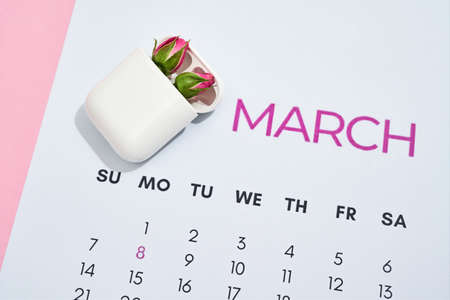 Charging case for earphones with two little pink roses inside on march calendar leaf over pink pastel background