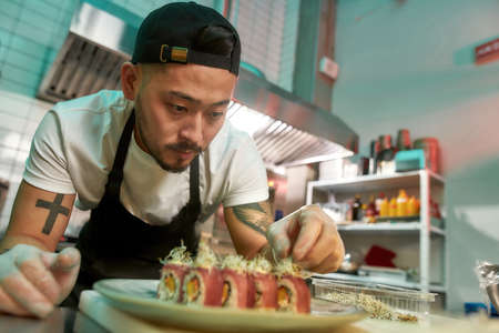 Portrait of experienced sushi chef carefully adding final touch with dedication to his delicious sushi set 免版税图像
