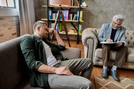 Relaxed young caucasian man during appointment with psychotherapist