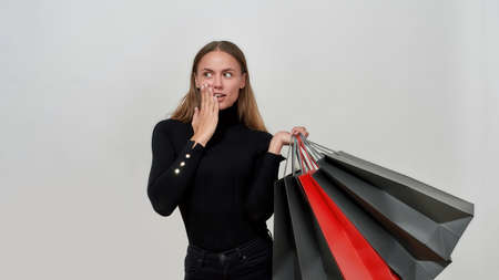 Surprised young caucasian woman wearing black clothes looking aside while holding bunch of shopping bags, posing isolated over light gray background