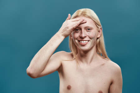 Shirtless young caucasian boy applying peeling mask