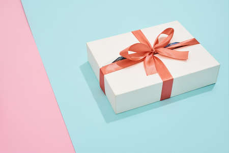 White gift box with red bow on pink and blue background