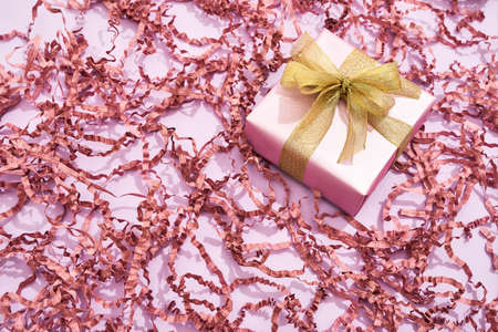 Romantic gift for Womens Day. Top view of a small wrapped gift box with golden bow on pink background with decorative straw 免版税图像