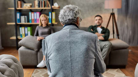 Rear view of psychotherapist talking to depressed couple