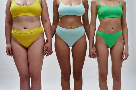 Cropped shot of three women with different body shapes in colorful underwear holding hands, supporting each other, standing together isolated over light background