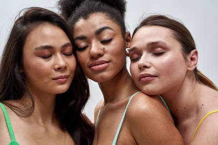 Close up portrait of three sensual diverse women posing together with eyes closed isolated over light background Foto de archivo