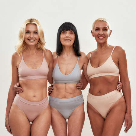 Three attractive middle aged women in underwear embracing each other while posing together on light background Foto de archivo