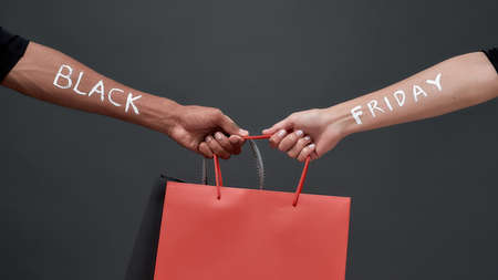 Hands of with Black Friday inscription sharing bags Stock Photo