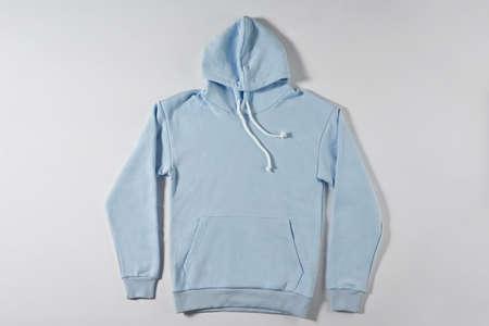 Blue jacket with a hood lies on a light background