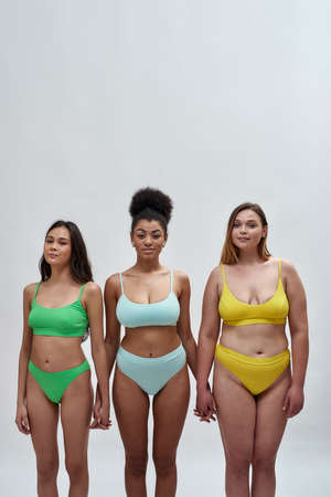 Three beautiful multiethnic women with different body shapes in colorful underwear holding hands, looking at camera, standing together isolated over light background