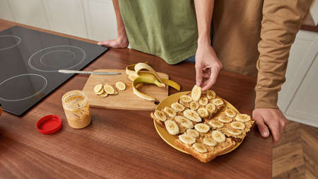 Young pair putting banana on toast in kitchen