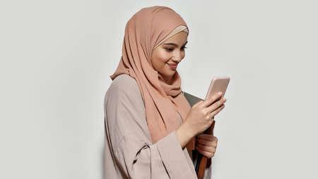 Cheerful arabian girl student in hijab using smartphone