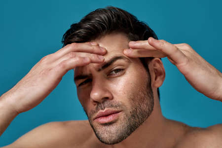 Closeup portrait of shirtless handsome guy checking his skin, looking for blemishes while posing isolated over blue background Archivio Fotografico