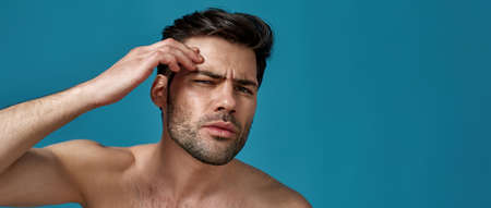 Studio portrait of shirtless man checking his skin, looking for blemishes, posing isolated over blue background
