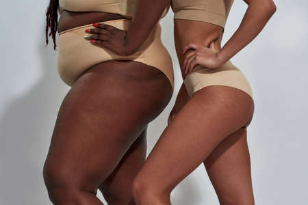Cropped shot of body of african american women in underwear with different body shape holding hand on waist standing together isolated over gray background
