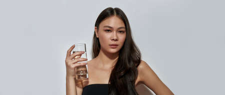 Cute young asian woman holding glass with water Foto de archivo