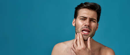 Portrait of shirtless handsome brunette guy checking his facial skin, looking at camera isolated over blue background