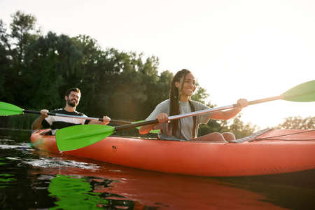 Happy young woman and her boyfriend enjoying kayaking together in a lake on a late summer afternoon