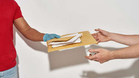 Close up of delivery man in protective gloves reaching out hands, giving parcels and envelops to a customer isolated over light gray background