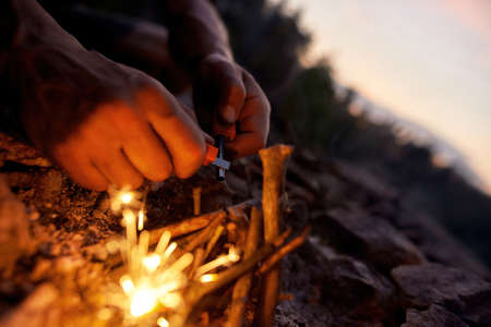 Close up of male hands making a fire with flint and steel in the wild