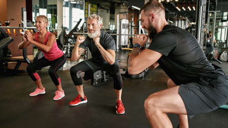 Highly motivated mature couple doing squats together with trainer