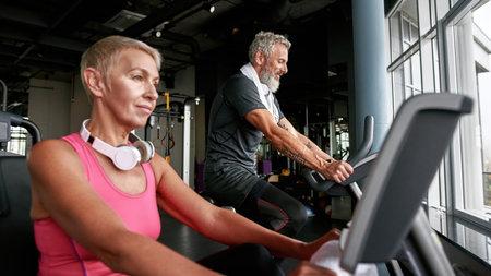Senior couple doing cardio exercise on bikes in gym Standard-Bild