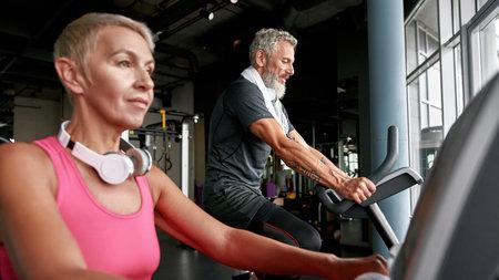 Senior woman and man doing cardio exercise on gym bikes
