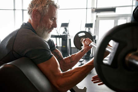 Portrait of strong aged man with strain arm muscles