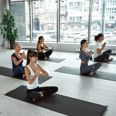 Smiling diverse women practice yoga train indoors together Standard-Bild