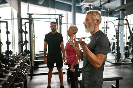 Senior man exercising in gym with dumbbell weights Standard-Bild