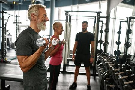 Elder man enjoying gym workout with dumbbells