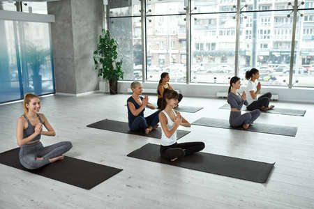 Happy multiethnic women have yoga session meditate indoors