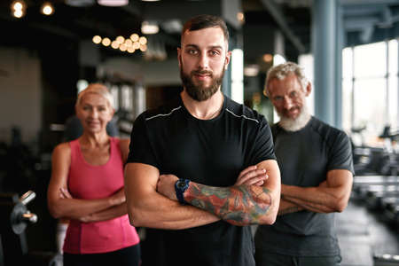 Young confident fitness coach posing with hands crossed Standard-Bild