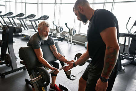 Aged powerlifter and young spotter in gym