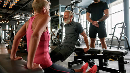 Athletic senior man smiling while hard workout at gym