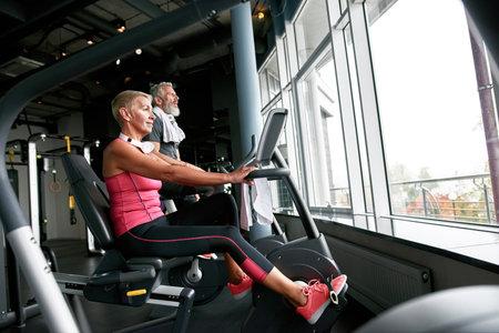 Happy senior citizens exercising in fitness center
