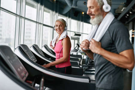 Healthy lifestyle concept. Mature woman working out on treadmill Standard-Bild