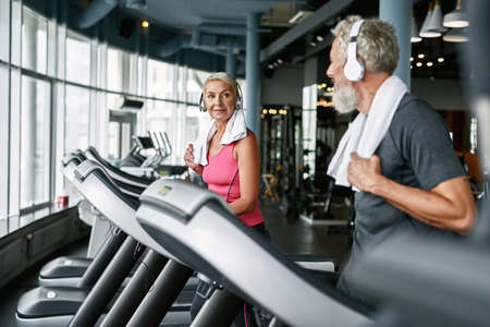 Sporty seniors exercising together in modern gym
