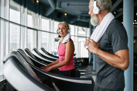 Living active life after retirement. Attractive senior woman on treadmill. Standard-Bild