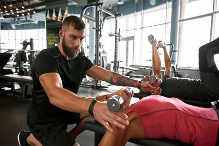 Athletic handsome personal trainer with aged female client