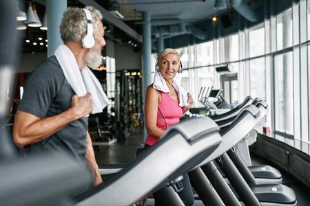 Happy senior couple on treadmills in gym