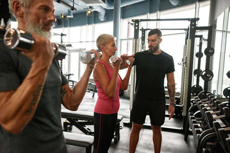Determined senior woman and man with dumbbells in gym
