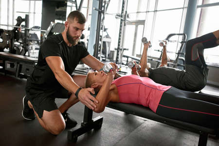 Older woman and young male coach in gym