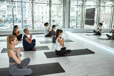 Sporty diverse female group practice yoga indoors